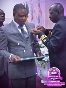Lt. Commander Alex Amankwaah pins an insignia of excellence on the breast pocket of Bishop Kofi Adonteng Boateng.