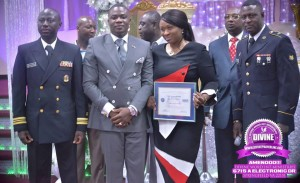 Behind every great man, there is a woman. Here Mrs. Elsie Adonteng Boateng proudly helps her husband with the plaque he received.